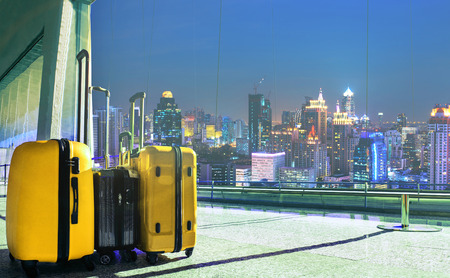 light duty: Traveling luggage in airport terminal with night scene of high building in city