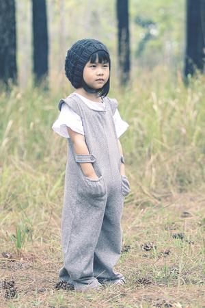 소나무 나무에 양모 두건 서 입고 사랑스러운 아시아 어린이의 초상