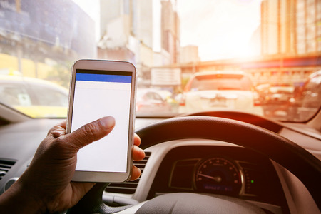 man driving car in urban traffic and touching  on smart phone application screen