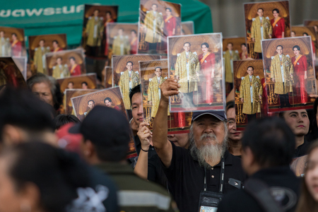 BANGKOK THAILAND - OCTOBER5,2017 : thai mourners people wearing black clothes and carrying king and queen of rama ix bhumibol photograph on last day of respect to their beloved king at grand palace