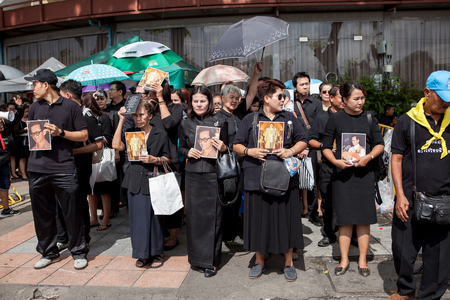 BANGKOK THAILAND - OCTOBER5,2017 : thai mourners people wearing black clothes and carrying  photograph of king bhumibol on last day of respect to their beloved king at grand palace 新聞圖片