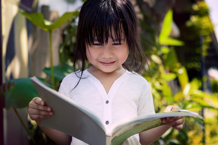 asian children reading a book in home garden