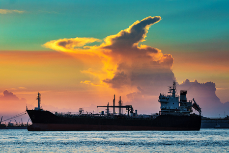 olie containerschip drijvend in petrochemische industriehaven tegen mooie zonsonderganghemel Stockfoto