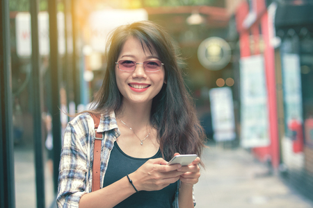 beautiful aisan woman toothy smiling face with smart phone in hand happiness emotion
