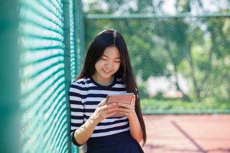 asian teen age reading social media in computer tablet happiness face