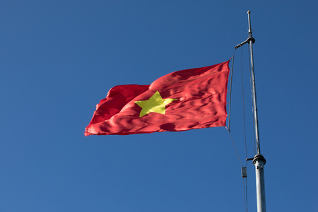 vietnam flag on top pole against beautiful clear blue sky
