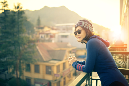 younger traveling woman standing outside building terrace and looking to destination scene against beautiful sun rise Фото со стока