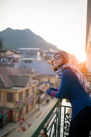 建物のテラスの外に立って、美しい太陽の上昇に対して目的地のシーンを探して若い旅行女性 写真素材