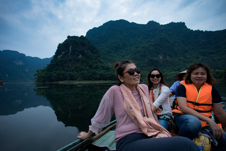 asian woman toothy smiling face happiness emotion sailing boat in ninh binh canal most popular traveling destination in vietnam Stock Photo