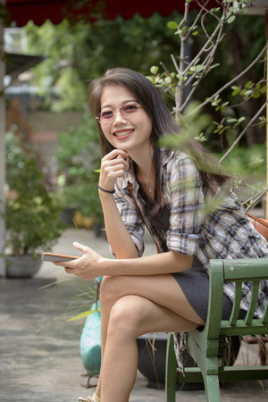 toothy smiling face of younger asian woman with smart phone in hand sitting in green park