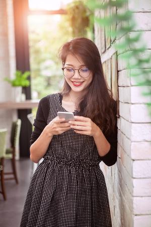 Aziatische jongere vrouw toothy lachend gezicht lezen bericht in slimme telefoon Stockfoto