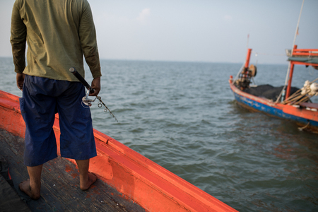 fisherman and fishing rod in hand standing on fishery boat
