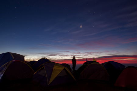 camping man standing in camping area against beautiful colorful sun rising sky 版權商用圖片