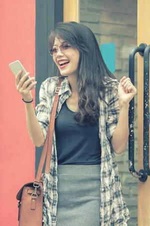 mooie jonge Aziatische vrouw op zoek naar slimme telefoon met geluk emotie