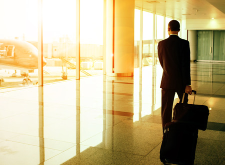 business man and traveling luggage walking in airport terminal  Stock Photo