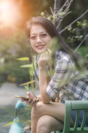 asian beautiful younger woman toothy smiling face and relaxing in garden