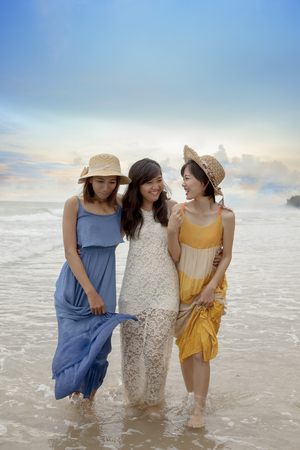 three asian younger woman relaxing happiness emotion on vacation beach Standard-Bild