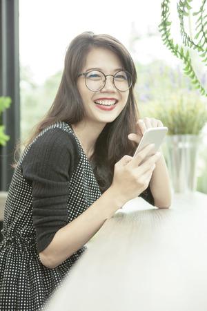 mooie Aziatische vrouw lachend gezicht geluk emotie met slimme telefoon in de hand