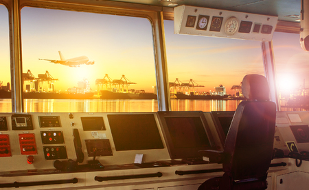 wheelhouse control board of modern industry ship approaching to harbor at night Stock Photo