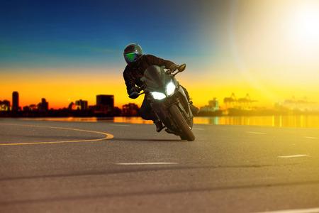 走行シーンの背景と鋭い曲線に傾くスポーツバイクに乗る男