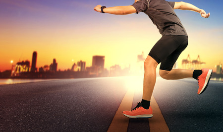 sport man jumping cross road traffic line against beautiful sunset sky Stock Photo