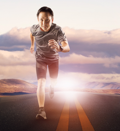 younger running man on asphalt highway against beautiful sunset sky and mountain scene