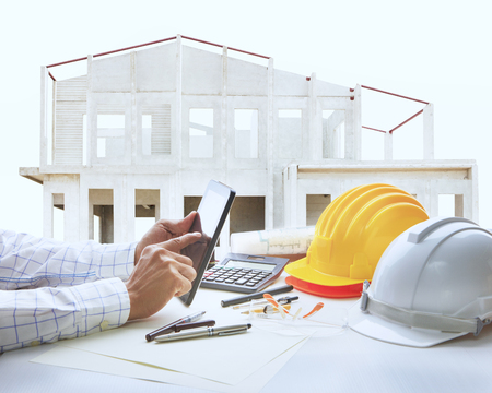 architect working table with house construction background