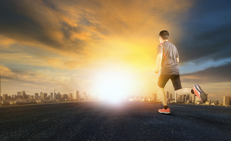 sport man running on asphalt road with sunset sky and urban scene background