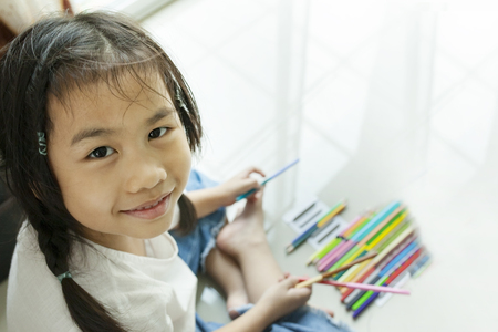 face of asian children playing color pencil on floor
