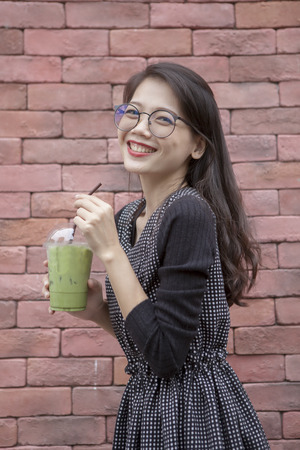 younger asian woman and glasses of ice green tea beverage in hand Stock Photo