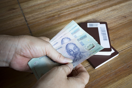 woman hand hold for counting vietnam dong banknote  with passport book on  wood table Stock Photo