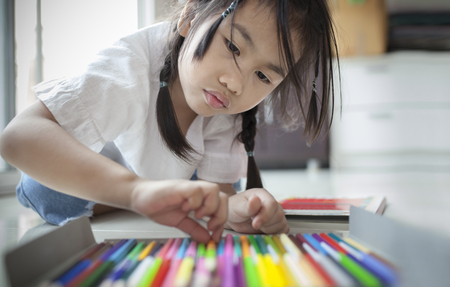 asian girl playing color pencil in home living room