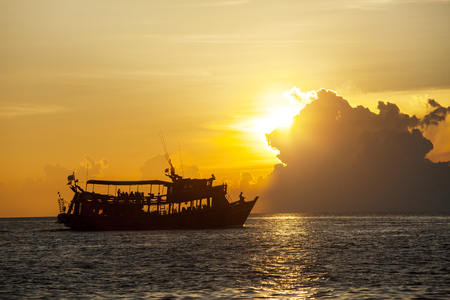 silhouete photography of beautiful sunset sky and tourist diving boat Stock Photo