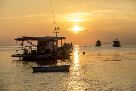 sea boat floating in harbor port against beautiful sunset sky at koh tao thailand 版權商用圖片