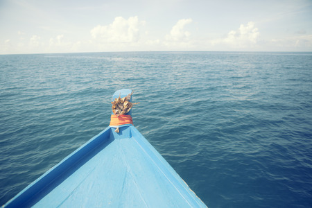 blue wooden boat cruising over deep sea