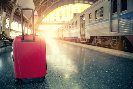 red traveling luggage in trains station