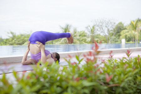 woman playing yoga beside swimming water pool with beautiful natural green leaves