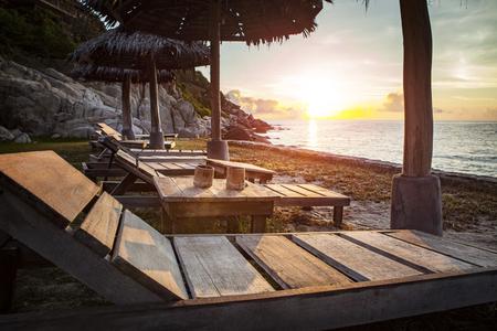 beautiful sunset sky and wood desk on sea beach