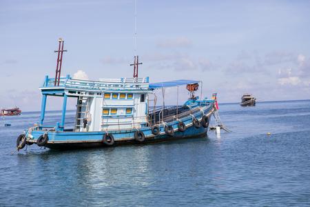 blue wood fishery boat floating on harbor port Stock Photo - 98099073