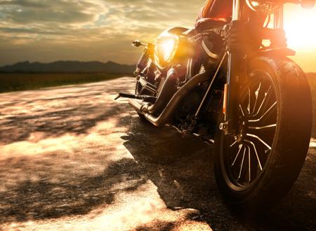 夕日の空の美しい光に対して田舎道を旅する古いレトロなオートバイ