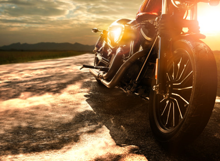 Old retro motorcycle traveling on country road against beautiful light of sunset sky Stockfoto