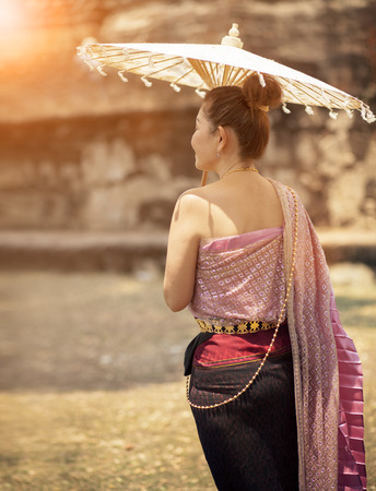 thai woman wearing old tradition clothes style with bamboo umbrella standing in ancient location 版權商用圖片