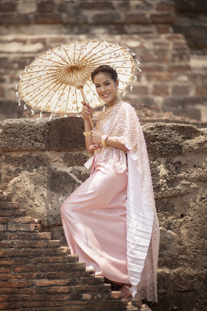 beatiful asian woman wearing thai traditon clothes style with wood umbrella  toothy smiling standing in ayutthaya heritage place