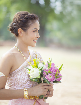 beautiful asian woman toothy smiling face and pink lotus flower in hand