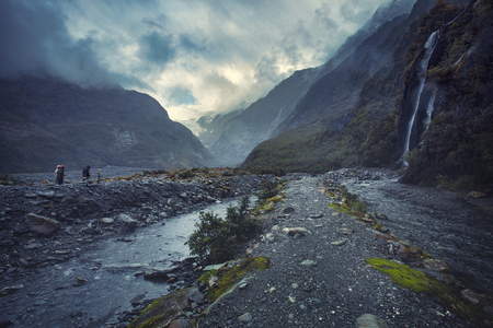 tourist walking on trail to franz josef glacier in foggy weather and rain drop