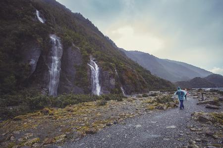 tourist walking on trail to franz josef glacier in foggy weather and rain drop
