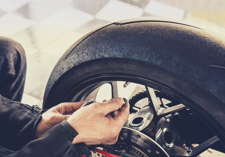 man checking air pressure of motorcycle wheel before traveling  Stockfoto