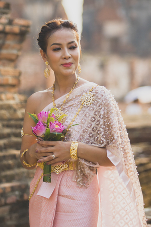 portrait of asian younger woman wearing thai tradition clothes holding pink lotus flower in hand toothy smiling face