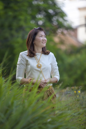 asian woman wearing thai period tradition clothes standing in green park