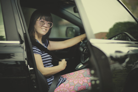 younger woman sitting on driver seat of suv car and fasten seat belt Stockfoto - 100124194
